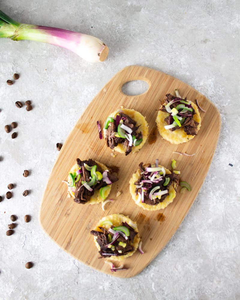 round polenta bites topped with lamb on a cutting board