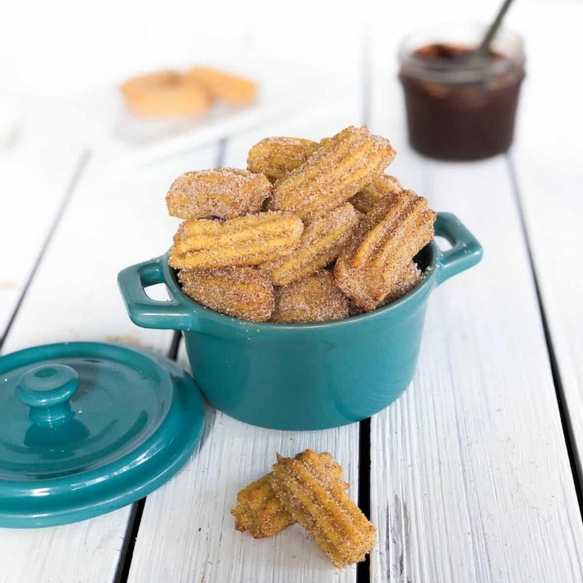 mini baked churro bites in a small crock with chocolate sauce in the background