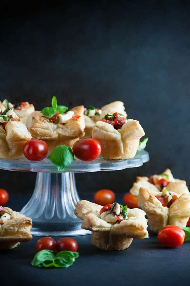 puff pastry cups filled with caprese salad on a clear platter with tomatoes and basil garnish