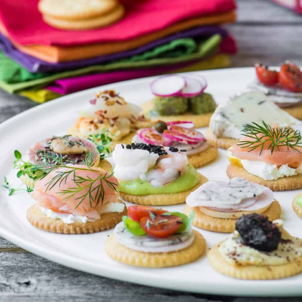 a colorful spread of crackers topped with different spreads and veggies on a white plate