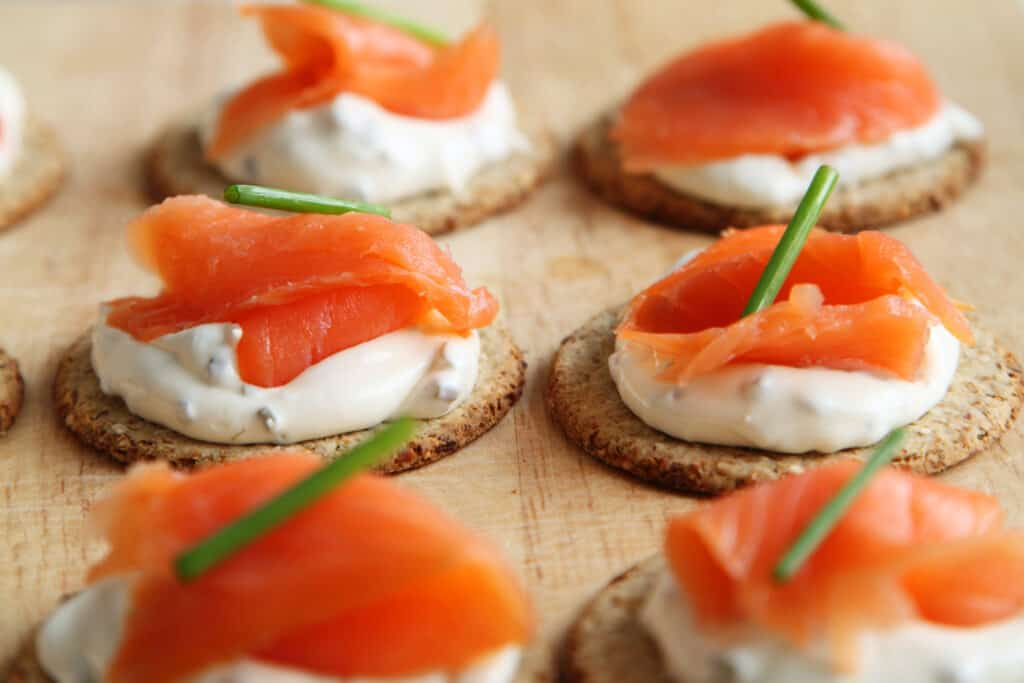 salmon and cheese on a cracker with a chive garnish