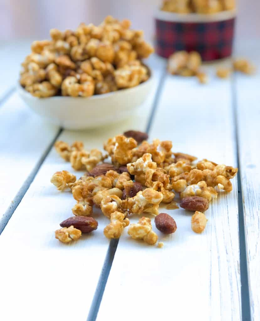 easy caramel popcorn recipe with almonds and peanuts on a table