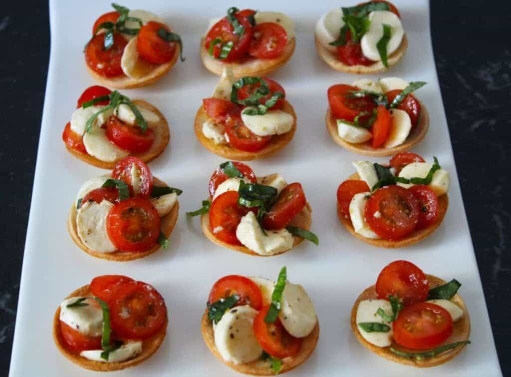 caprese salad over top of crunchy bread rounds on a white serving platter