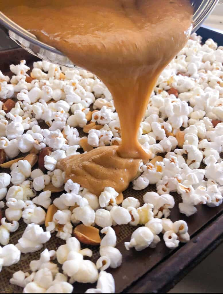 homemade popcorn on baking sheet being drizzled with caramel sauce