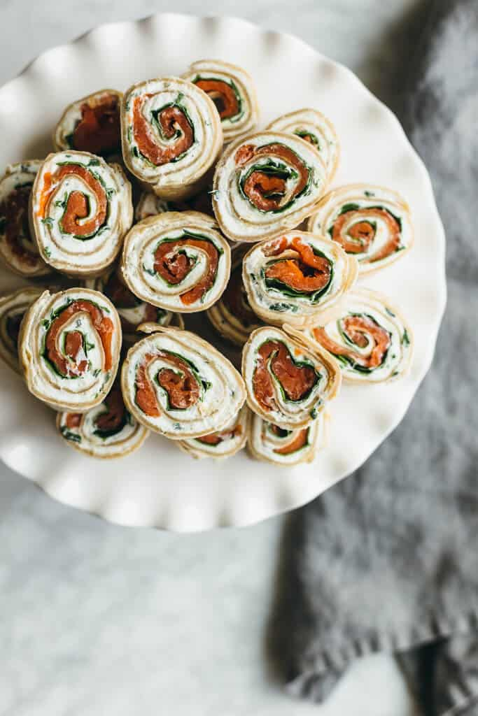 tortillas stuffed with chevre cheese spinach and salmon cut and stacked on a plate