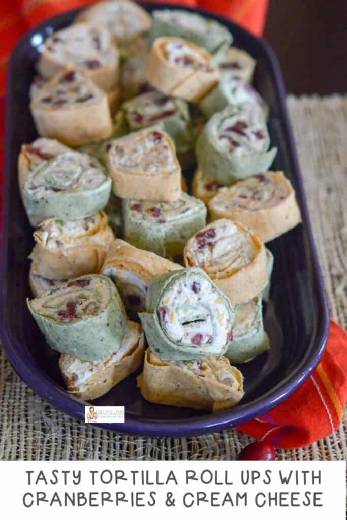 tortilla roll ups stacked on a cutting board with cranberries