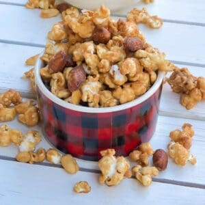 caramel popcorn and nuts in a red small bowl.