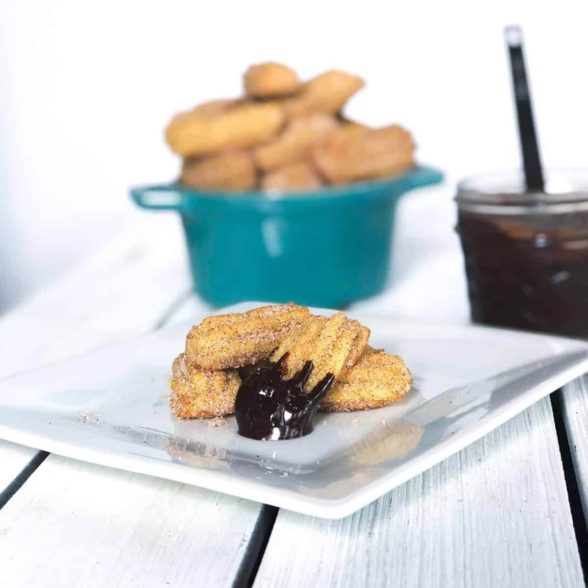 mini churro bites baked covered in chocolate sauce on a plate