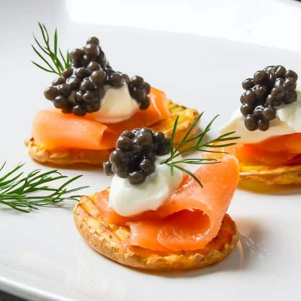 slices of salmon topped with a dollop of sour cream and caviar