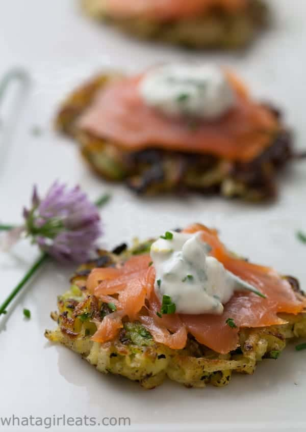 vegetable potato pancakes on a white plate topped with slices of salmon and a dollop of sour cream