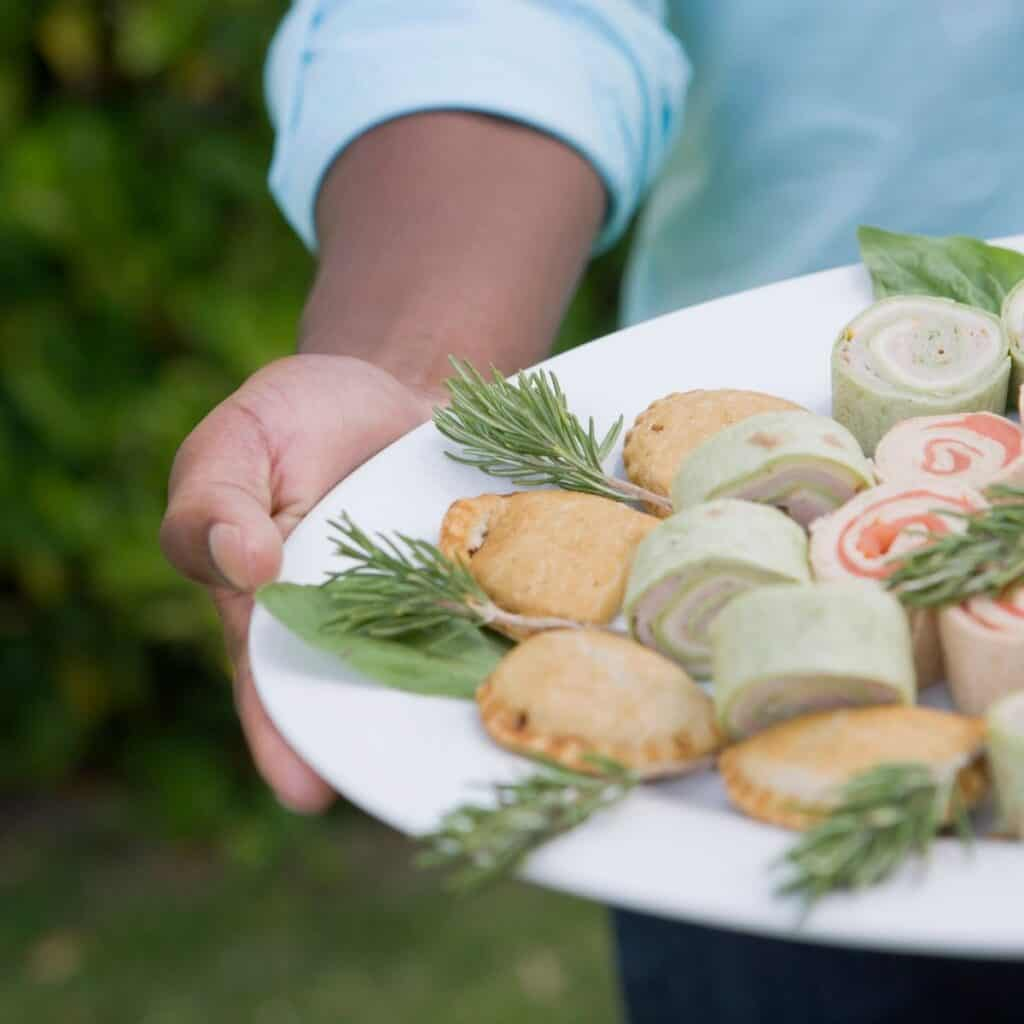 multiple finger food pinwheel sandwiches being served on a platter