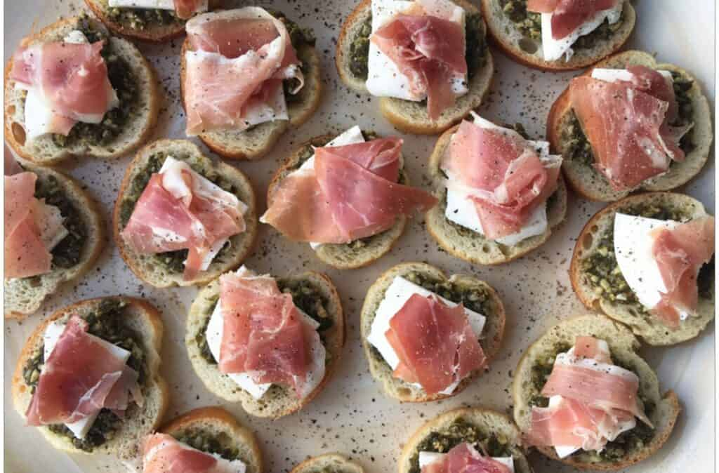 mini pesto crostini canapes topped with slices of pancetta