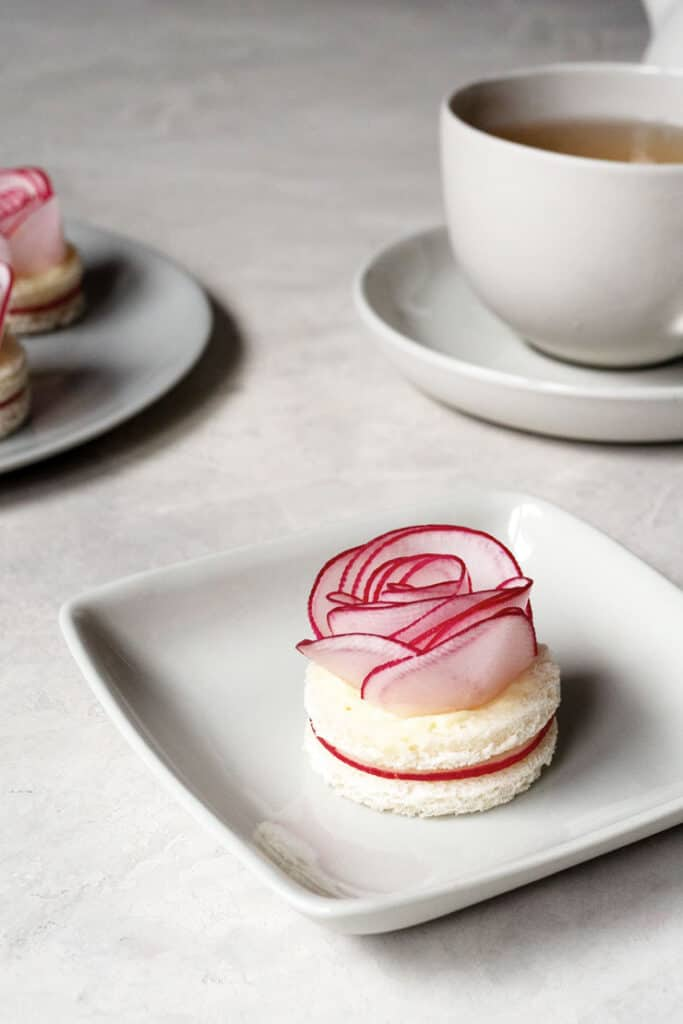 round tea sandwiches on a white plate topped with a beautiful radish rose