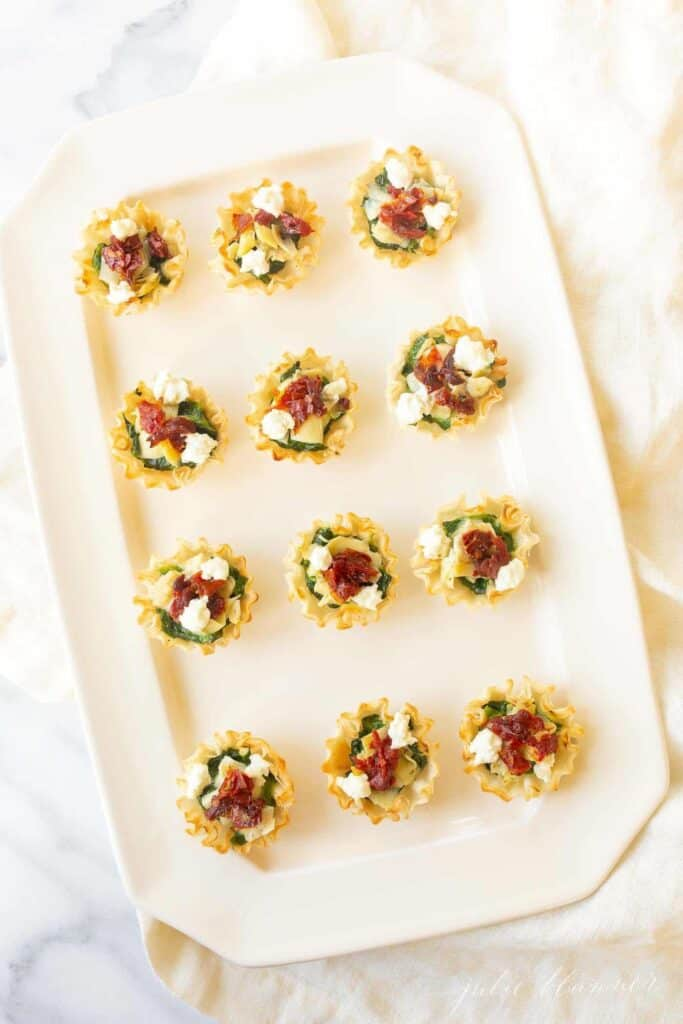 phyllo cups stuffed with spinach and artichokes on a white large serving platter