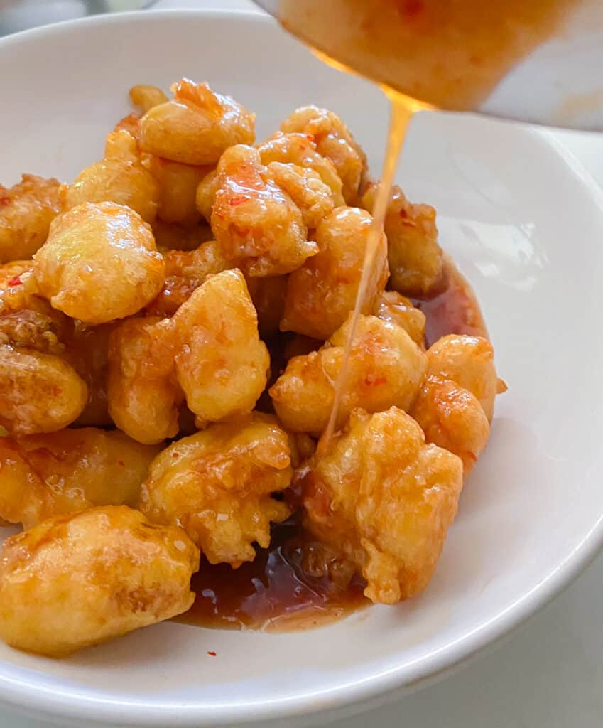 shot of bowl pouring chili sauce over top of fried shrimp in a bowl
