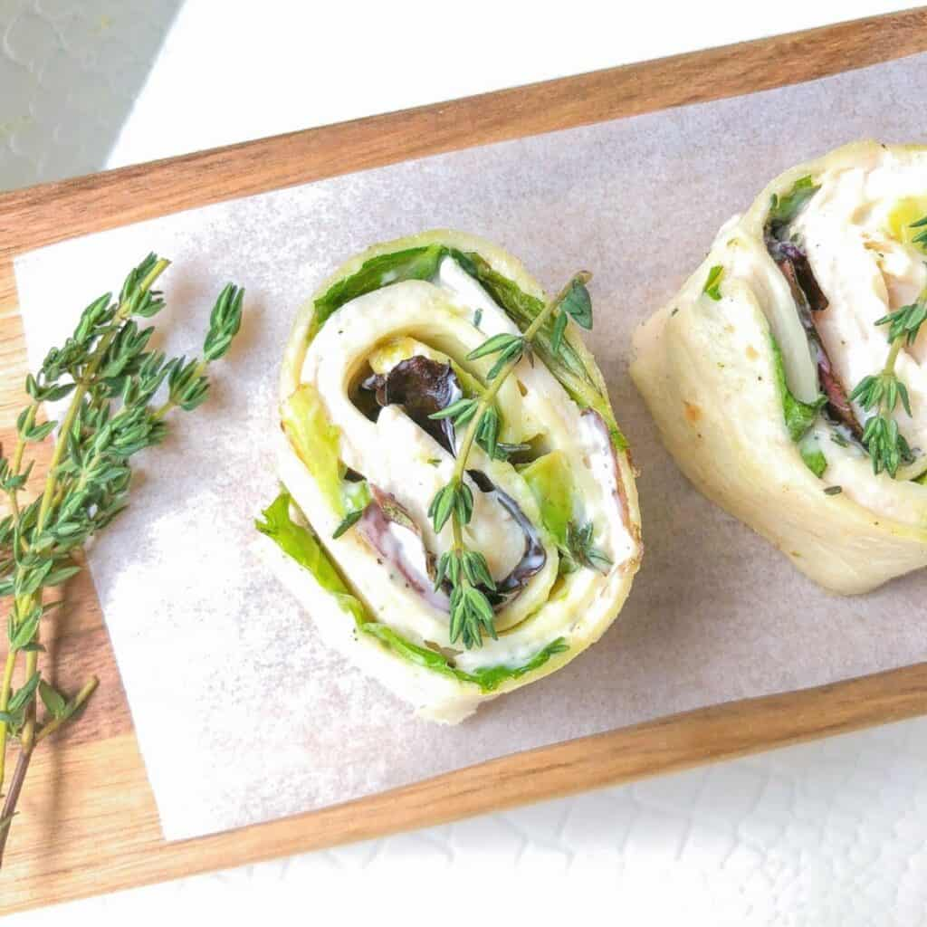 turkey roll ups with cheese, lettuce and dressing laid on a cutting board with fresh tyhme