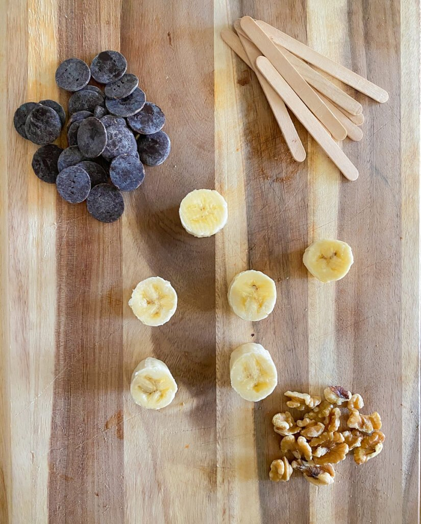 chocolate, bananas, Popsicle sticks, walnuts on cutting board