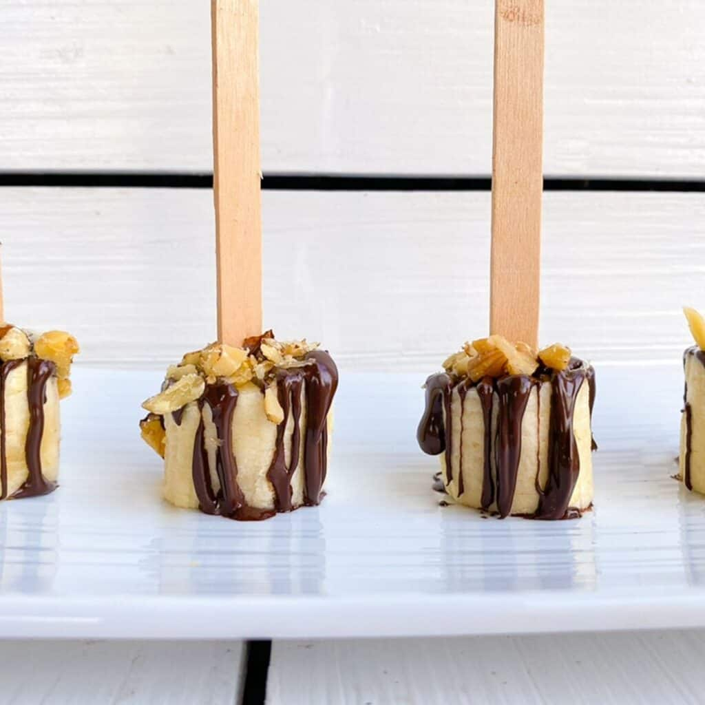 banana slices on popsicles sticks dipped in chocolate with nuts.