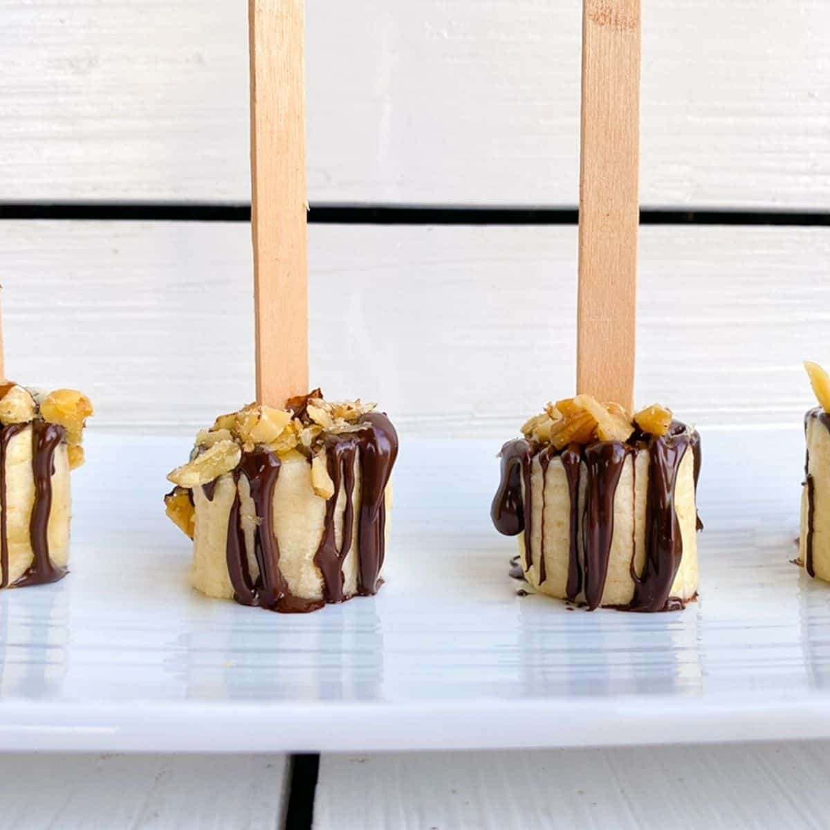banana slices on popsicles sticks dipped in chocolate with nuts