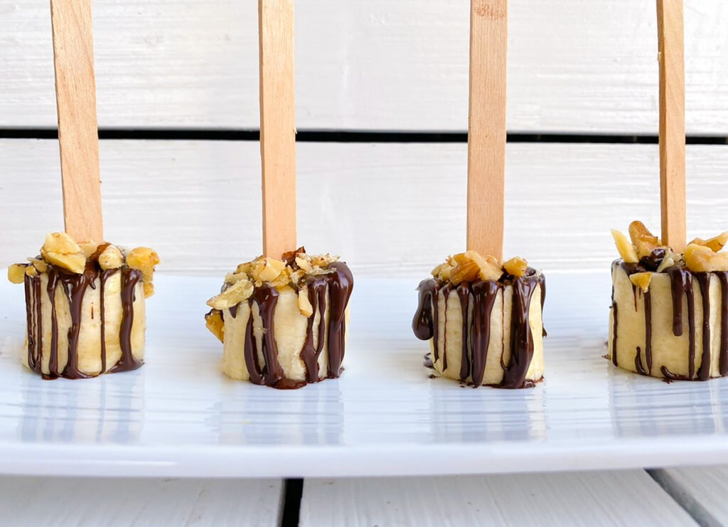 banana bites with chocolate sauce drizzle on top and chopped walnuts