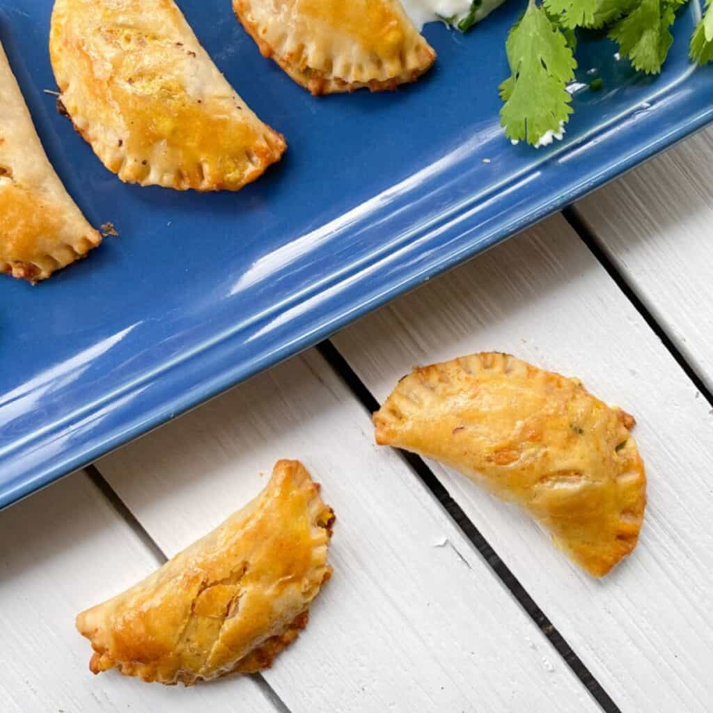empanadas on a blue plate and white table