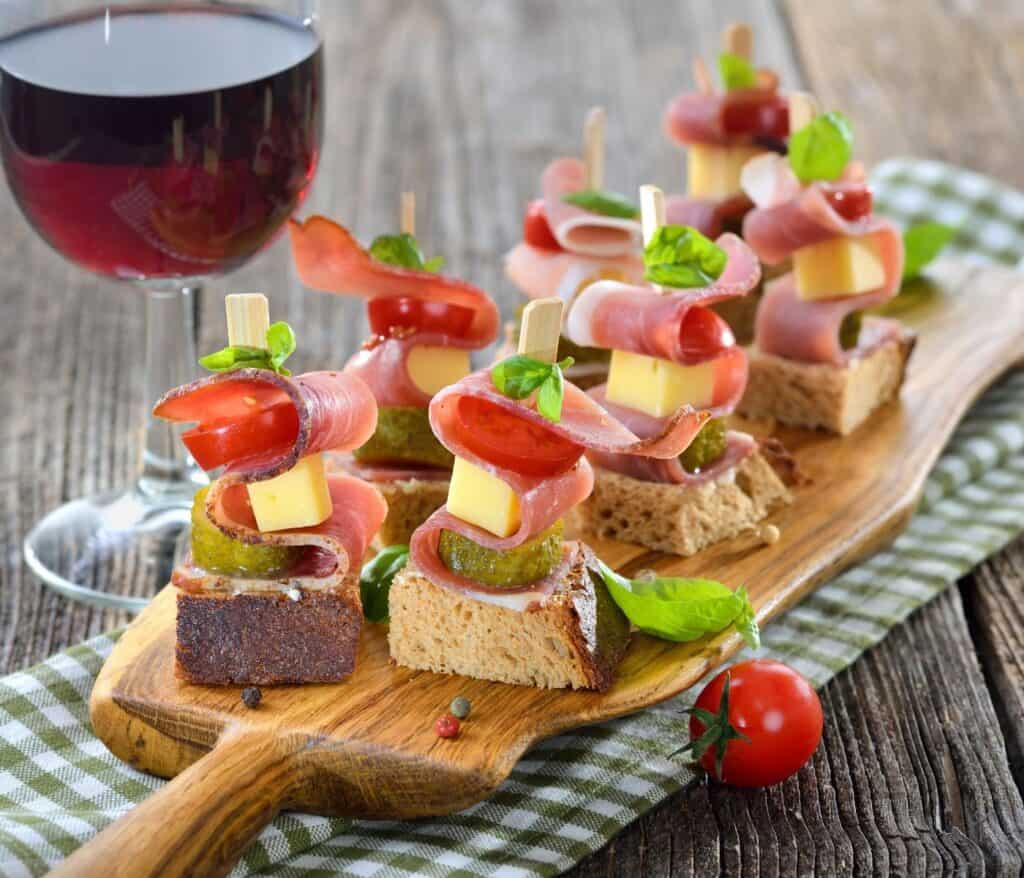 skewered meat bread and cheese skewers on a cutting board with a glass of wine