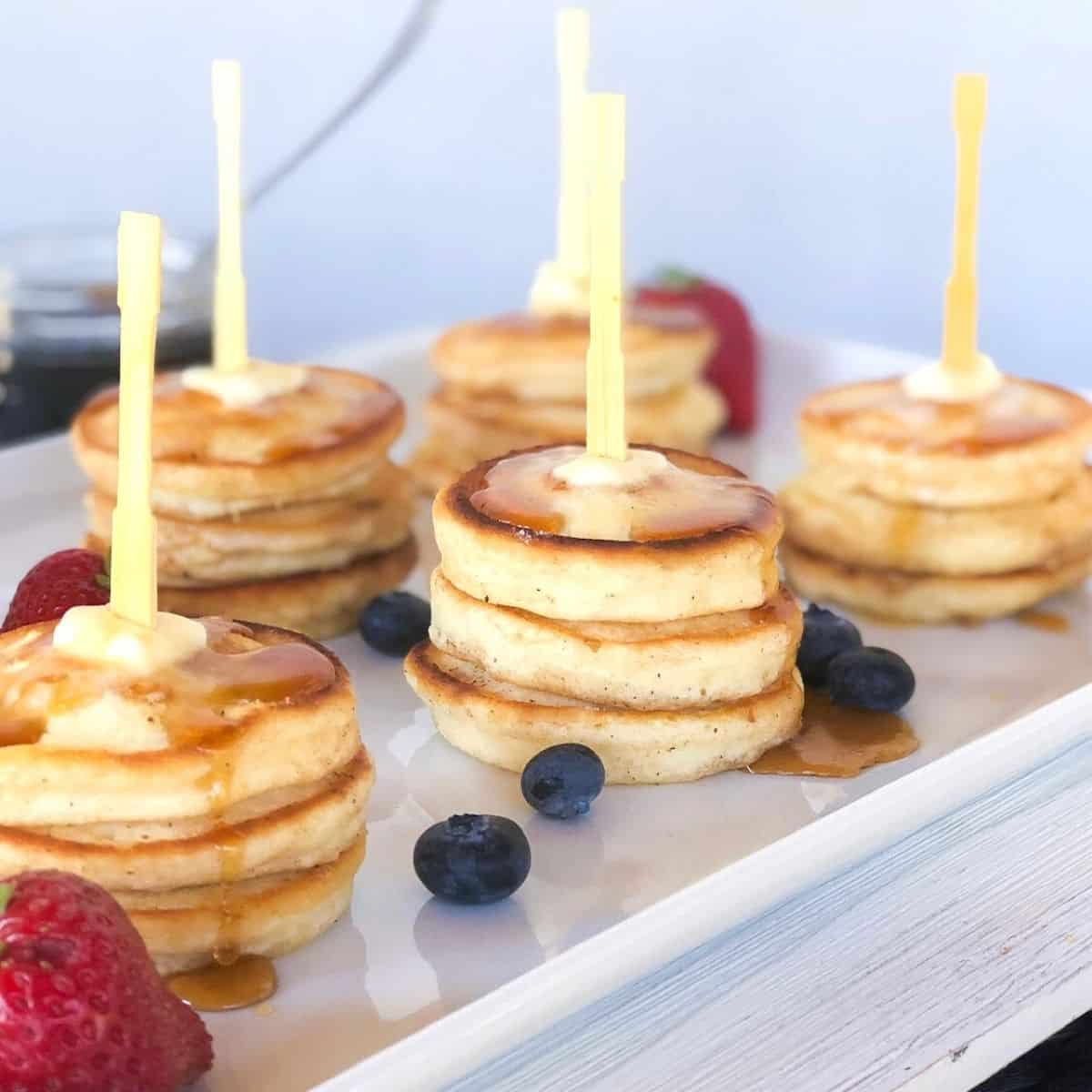 Mini silver dollar pancakes on wooden skewers with fruit.