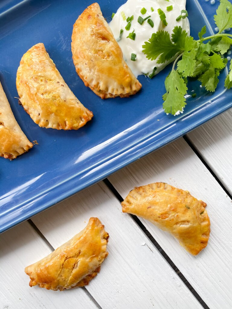 empanadas that are vegetarian on a long blue dish with sour cream and fresh cilantro