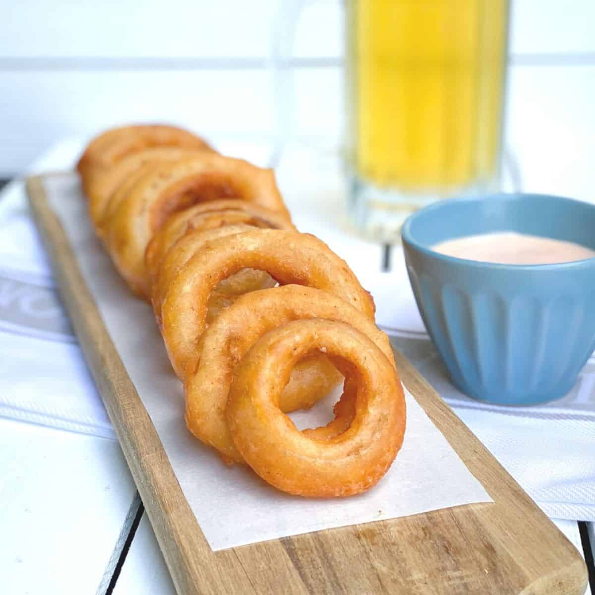 crispy beer battered onion rings on a wooden plank with dipping sauce and a beer on the side.