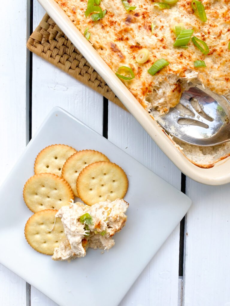 hot crab artichoke dip with cream cheese in a casserole dish with crackers on the side
