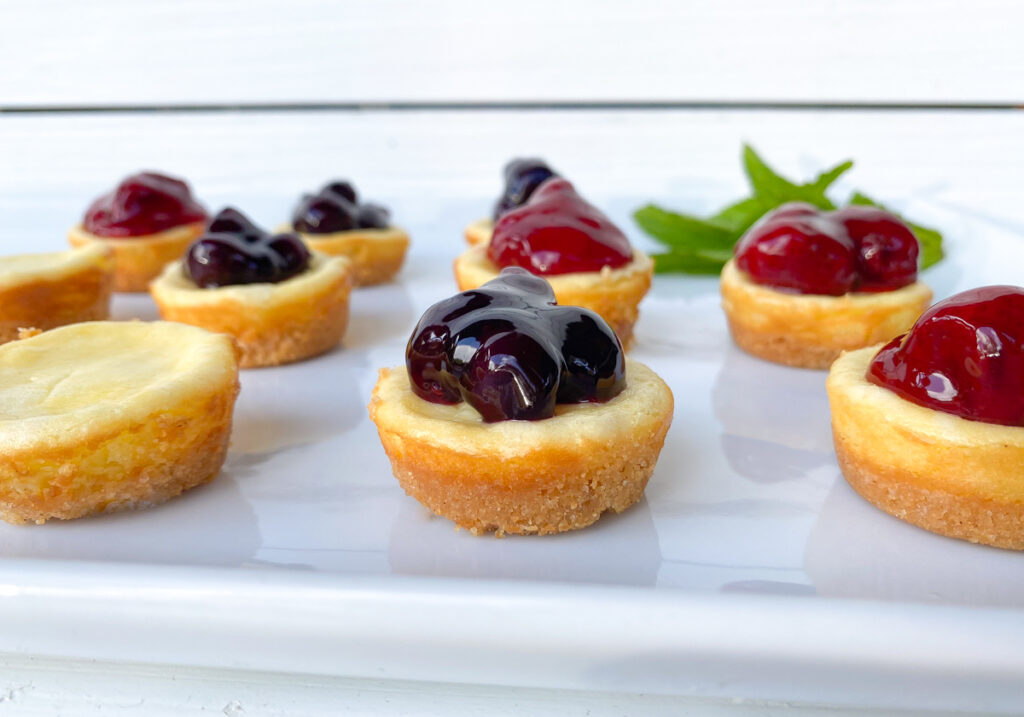 mini plain cheesecakes on a white plate topped with strawberries and blueberries
