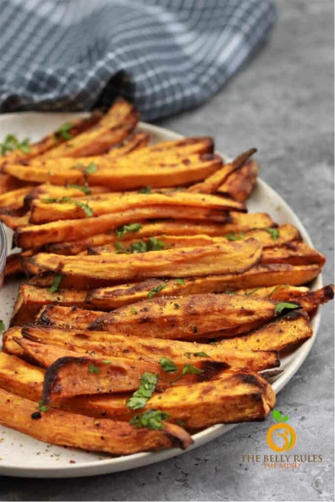 sweet potato fries on a flat white plate with herbs on top.