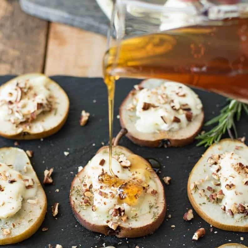sliced pear finger food topped with goat cheese and honey