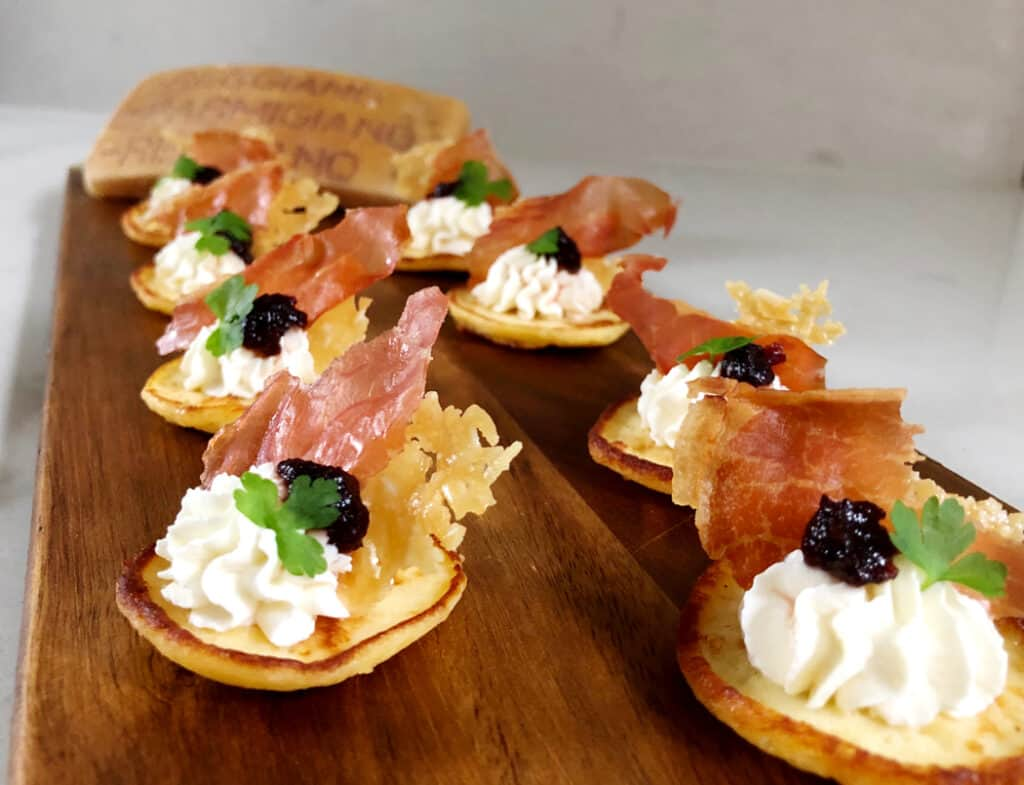 mini pancake finger food appetizer with cheese and proscuitto on top