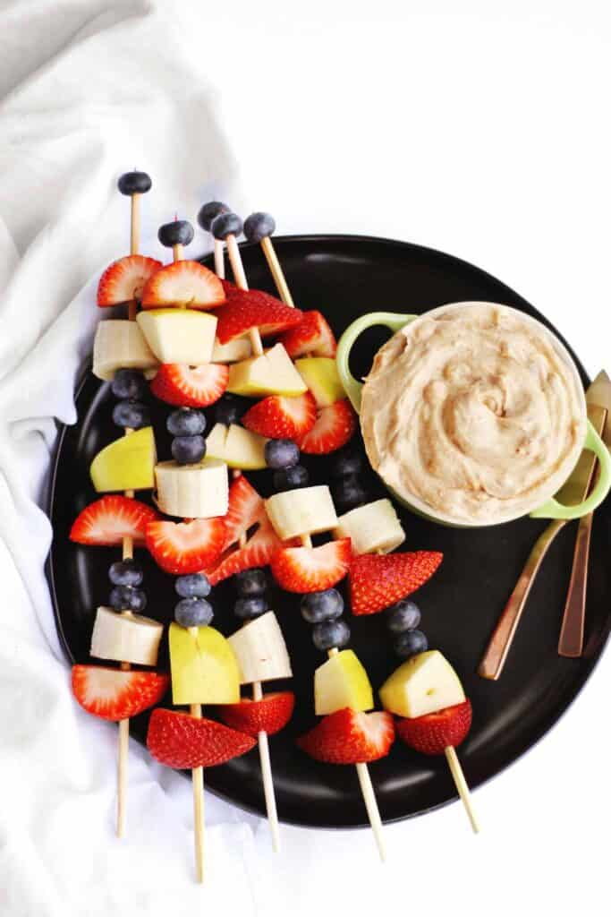 strawberries, bananas, apples and blueberries skewered with peanut butter dip on the side.