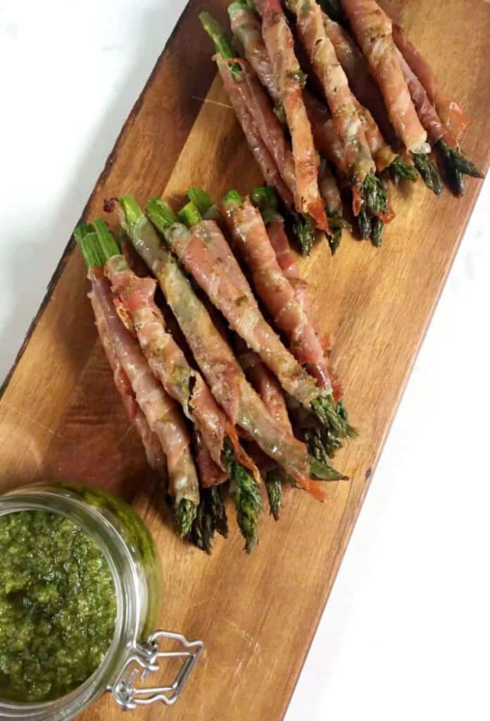 wrapped asparagus with prosciutto on a wooden plank for a party