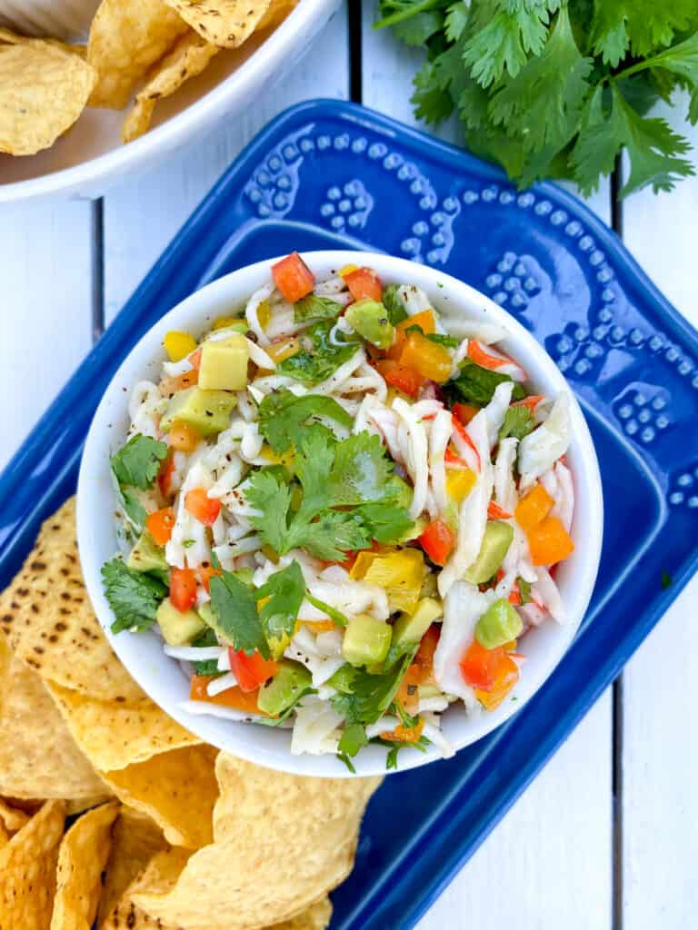 overhead shot of crab ceviche in a white bowl on a blue plate with tostitos