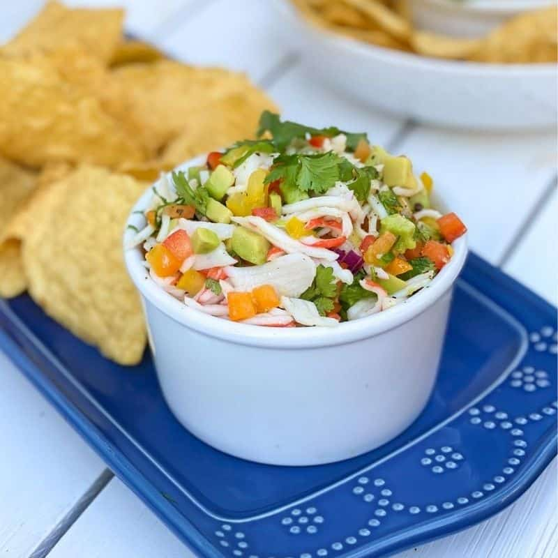 crab meat with peppers and onions in a white bowl with tortilla chips