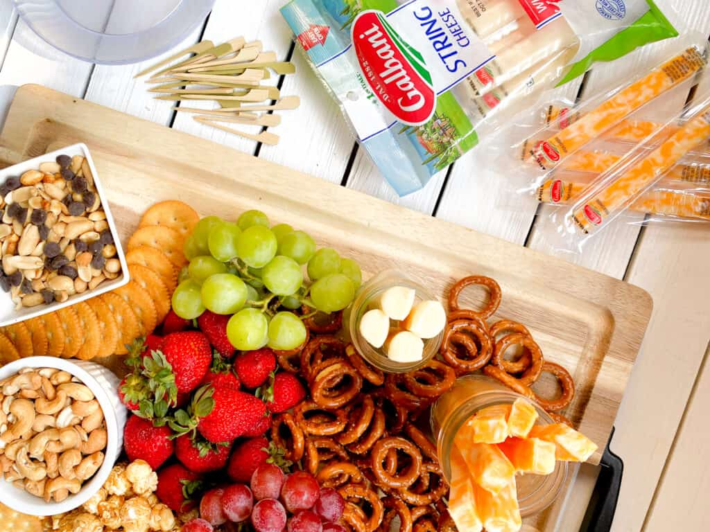 kid friendly charcuterie board with pretzels, nuts, cheeses and fruit