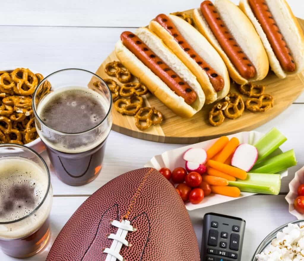 Hotdogs, beer, finger foods and a football on a table.
