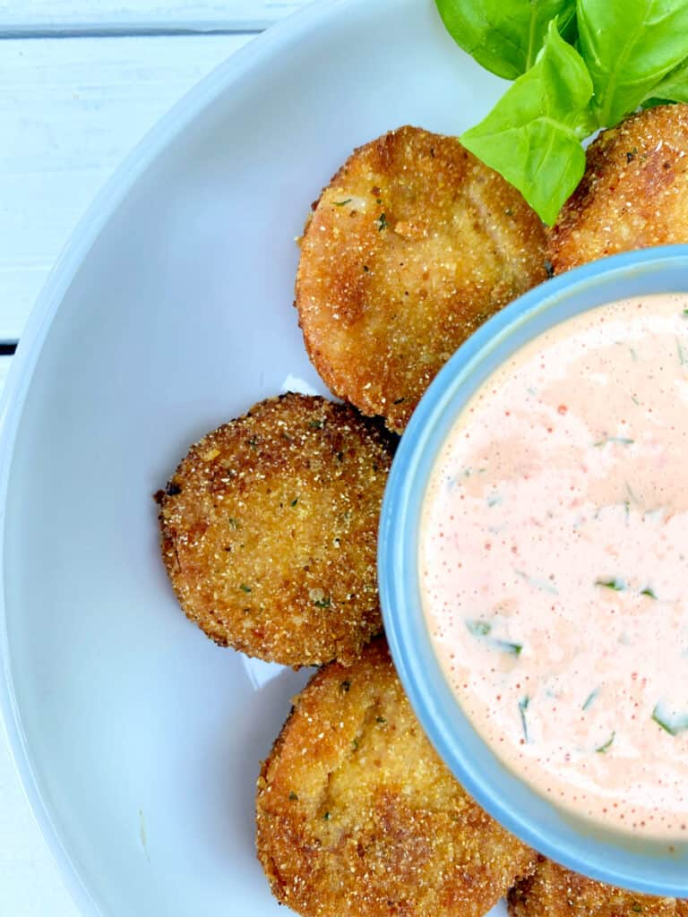 fried red tomatoes with red pepper dipping sauce in the middle