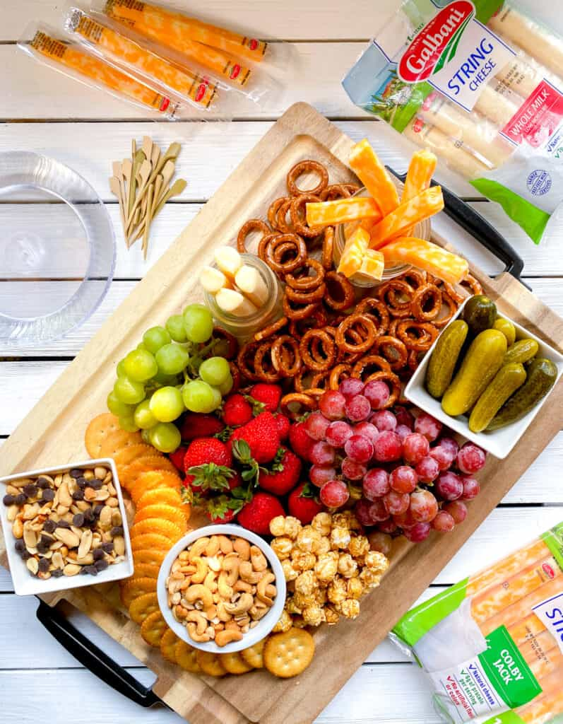 kids charcutetie board with cheese, pretzels, nuts and fruit.