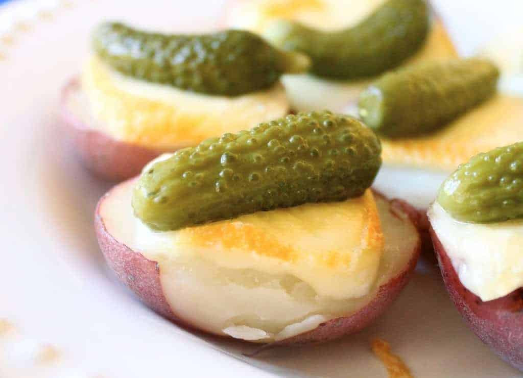 mini raclette finger food with potatoes and pickles on top