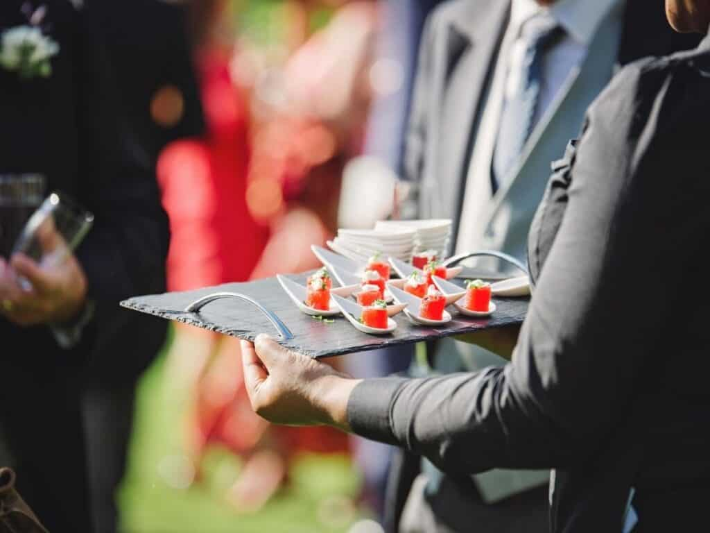 catered finger food watermelon bites on mini cups.
