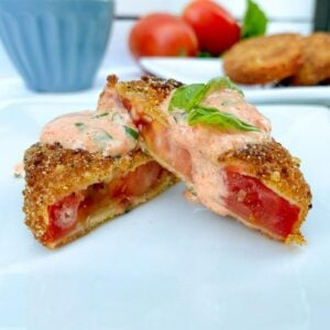 a fried red tomato with aioli sauce over top
