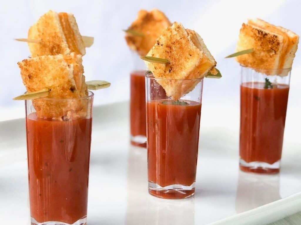 Grilled cheese cubes over top of tomato soup shooters.