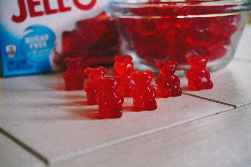 mini gummy bears standing up on a table with jello in the background.