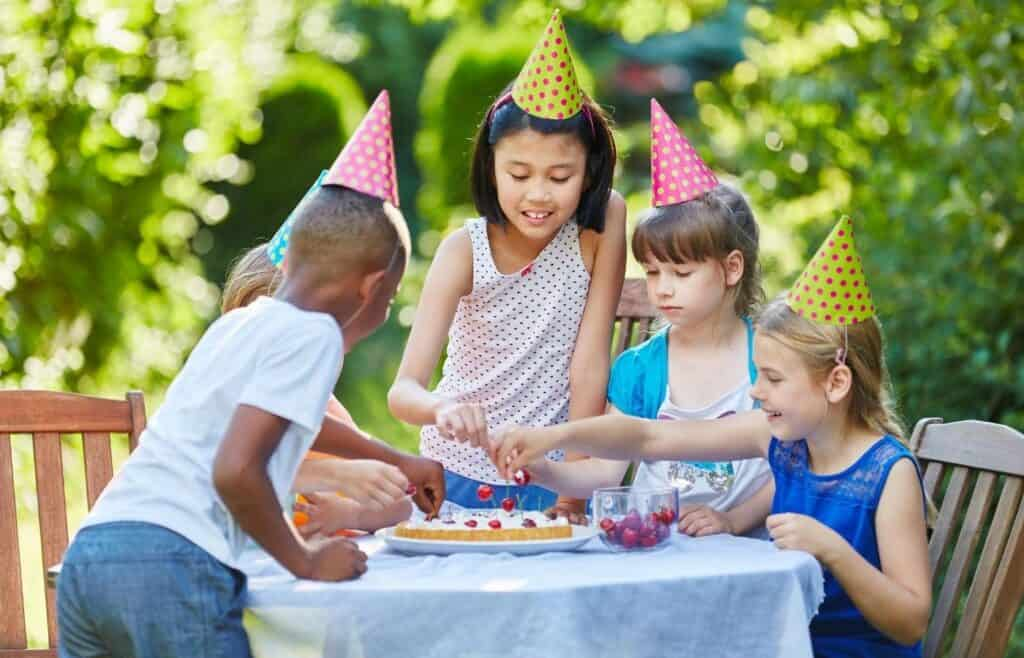 kids at a birthday party picking up cherries with their fingers.