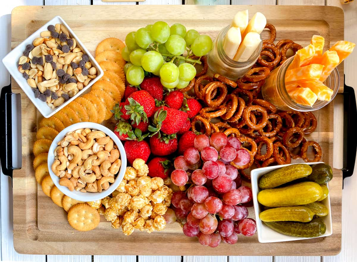 large charcuterie board for kids with cheese, nuts, fruit and snacks.