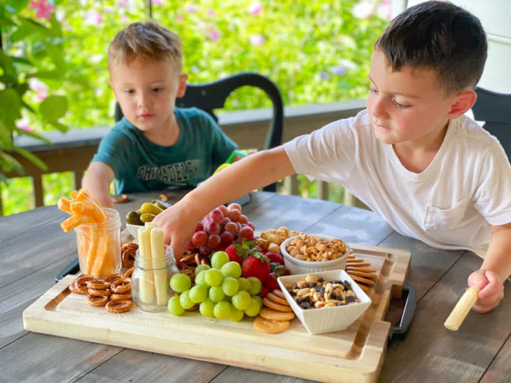two kids snacking on a large charcuterie board tray
